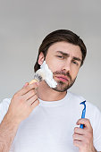 portrait of man with brush and razor in hands putting shaving foam on face on grey backdrop