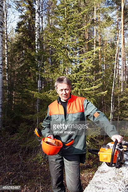 Portrait of man with chainsaw in forest