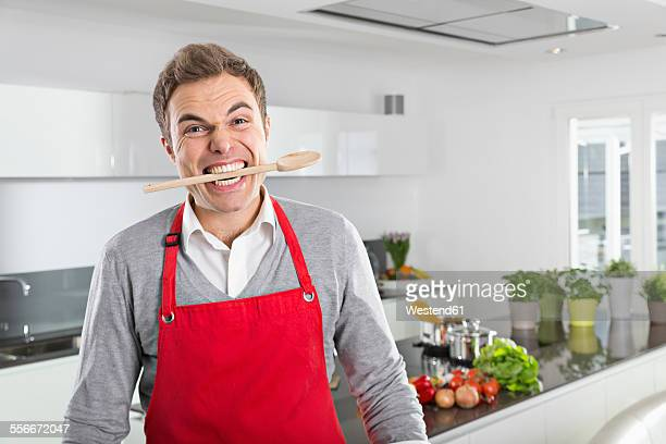 Portrait of man with cooking spoon between his teeth
