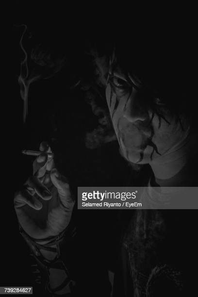 Portrait Of Man With Face Paint Smoking Cigarette In Dark