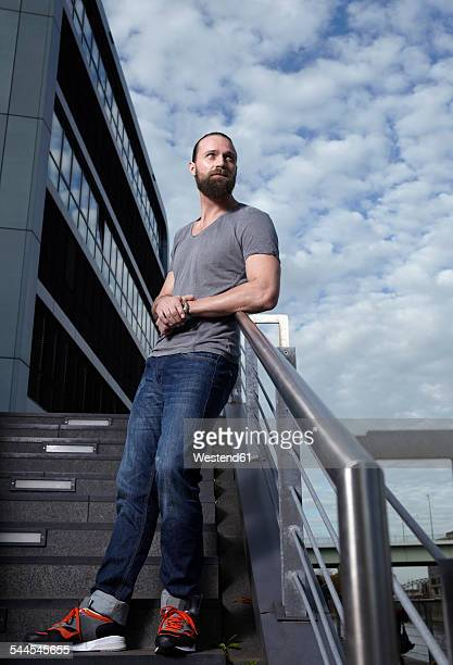 Portrait of man with full beard leaning on railing