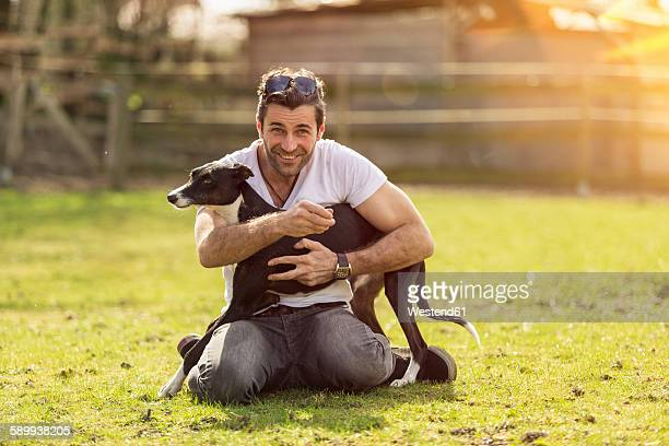 Portrait of man with his dog on a meadow
