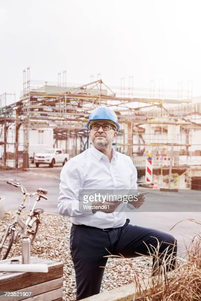Portrait of man with tablet wearing hart hat at construction site