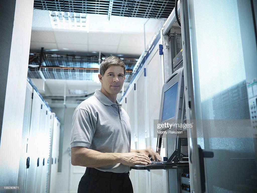 Portrait of man working on computer in computer server room