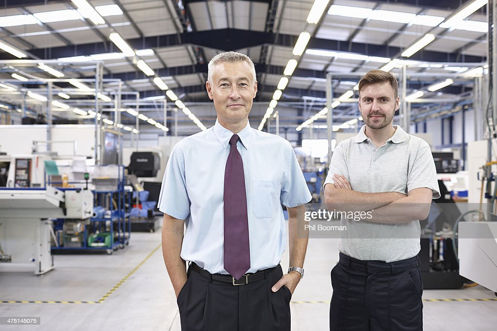 Portrait of manager and co-worker in engineering factory