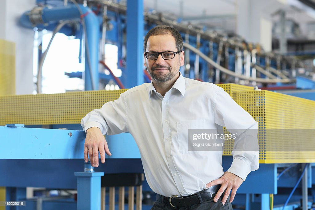 Portrait of manager and industrial machinery