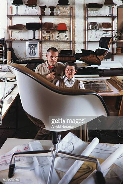 Portrait of married American designers Charles and Ray Eames as they pose behind one of their chairs which sits on a table in their studio Venice...