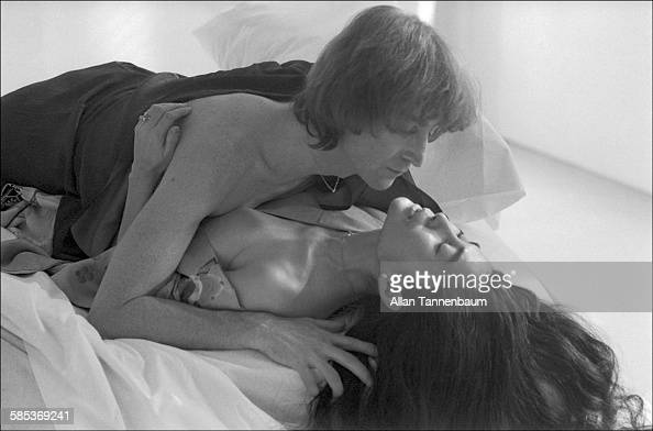 Portrait of married musicians John Lennon and Yoko Ono as they lie together on a bed in a SoHo gallery New York New York November 26 1980 The gallery...
