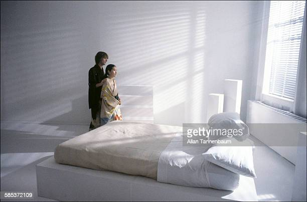 Portrait of married musicians John Lennon and Yoko Ono both dressed in kimonos beside a bed in a SoHo gallery New York New York November 26 1980 The...