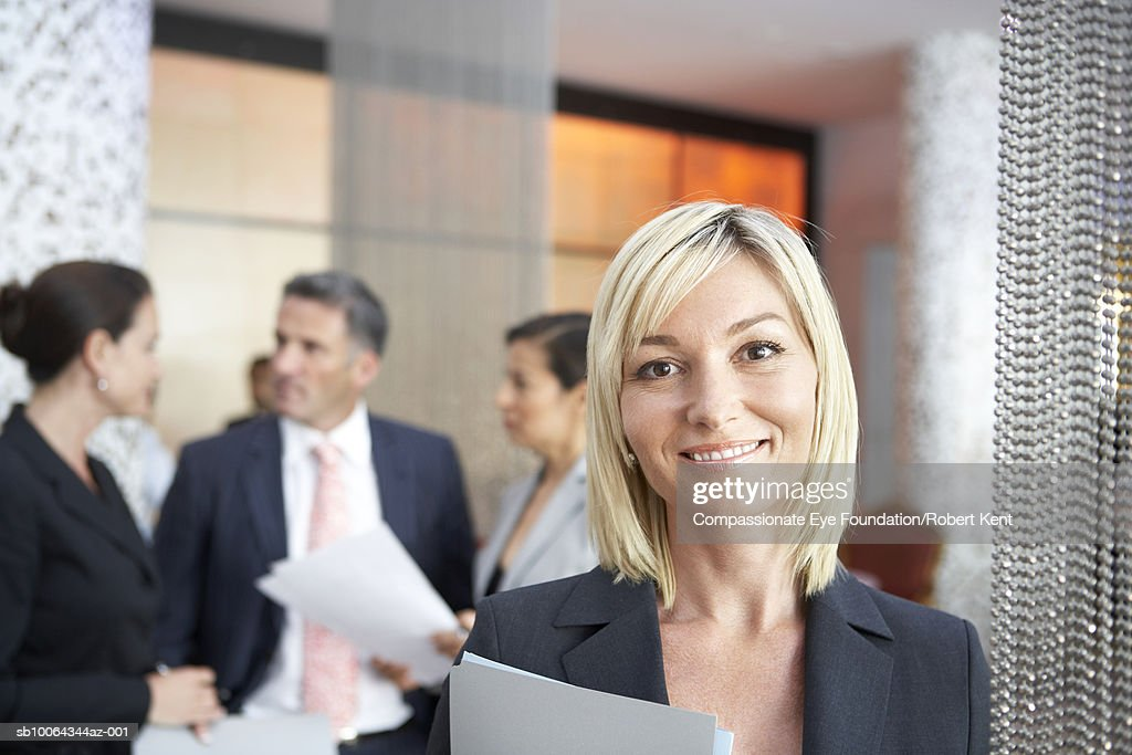 Portrait of mature business woman, others in background : Stock Photo