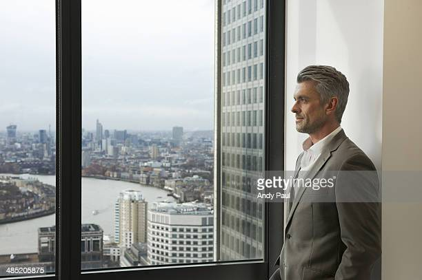 Portrait of mature businessman looking out of office window, Canary Wharf, London, UK