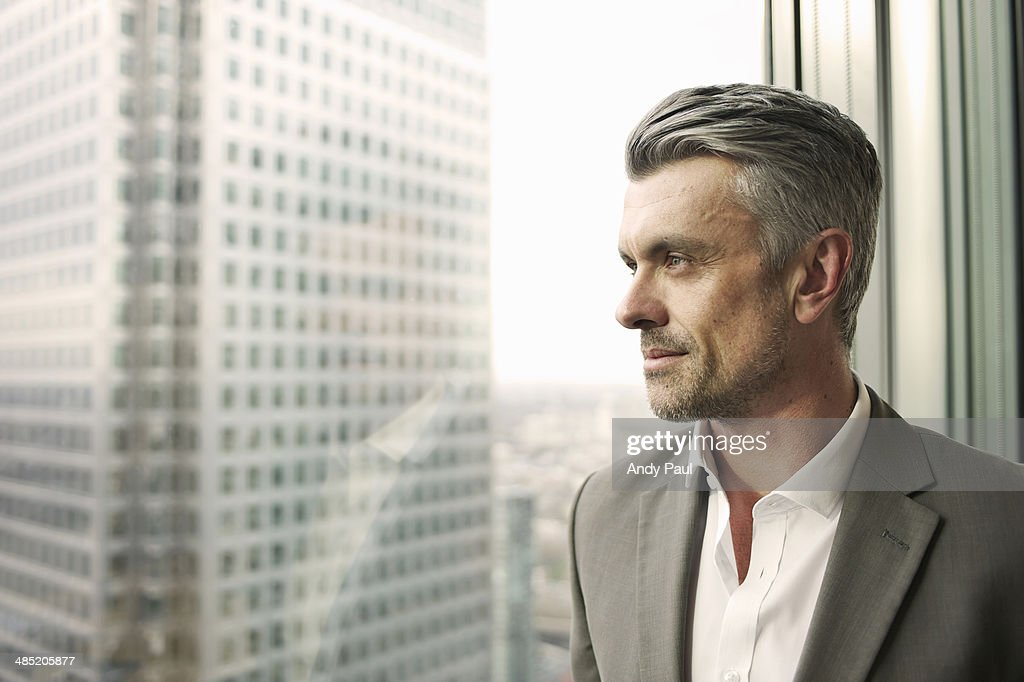 Portrait of mature businessman looking out of office window : Stockfoto