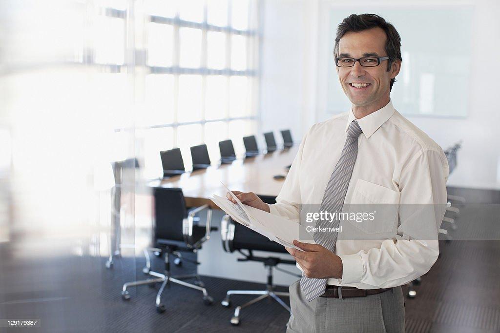 Portrait of mature businessman reading documents : Stock Photo