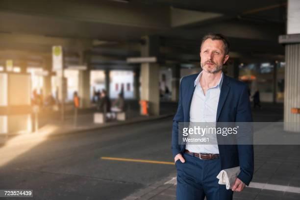 Portrait of mature businessman waiting at bus terminal