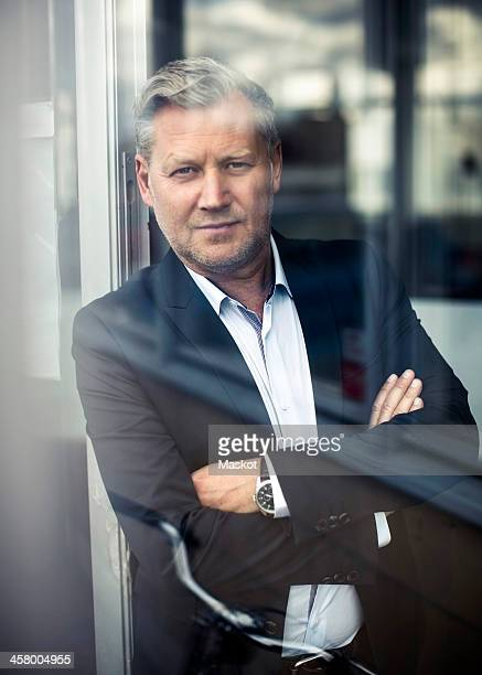 Portrait of mature businessman with arms crossed leaning in office