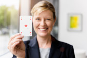 Portrait of mature businesswoman holding up ace playing card