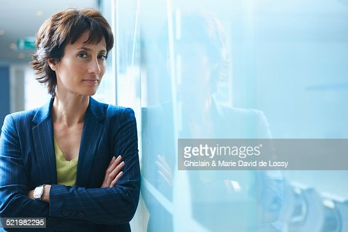 Portrait of mature businesswoman leaning against glass wall with arms crossed
