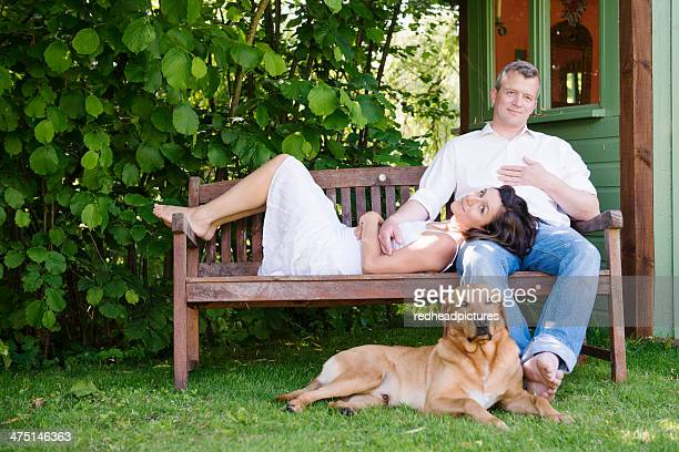Portrait of mature couple on garden bench with dog