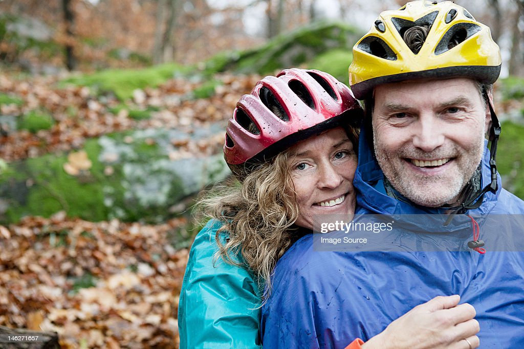 Portrait of mature couple wearing cycling helmets in forest : Stock Photo