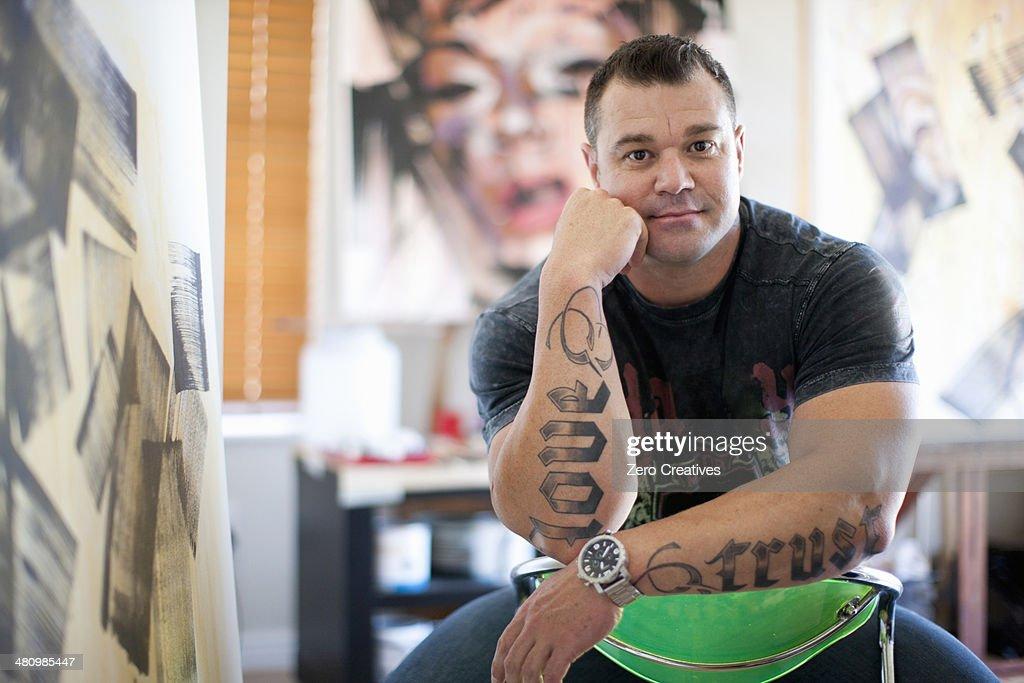 Portrait of mature male artist sitting in studio