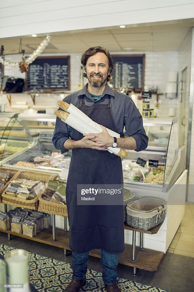 Portrait of mature male baker holding loaves of bread in supermarket : Photo
