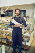 Portrait of mature male baker holding loaves of bread in supermarket