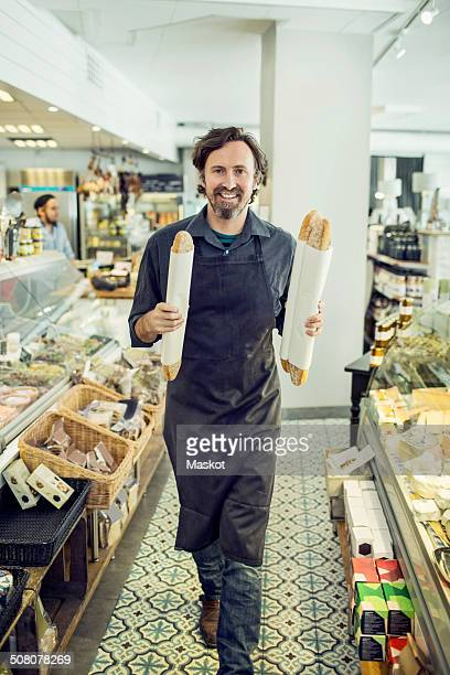 Portrait of mature male baker with loaves of bread walking in supermarket