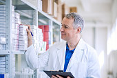 Portrait of mature male pharmacists working in modern drugstore. Perfect medication. Shot of a mature pharmacist looking for an ordered drug on a shelf at the local pharmacy.