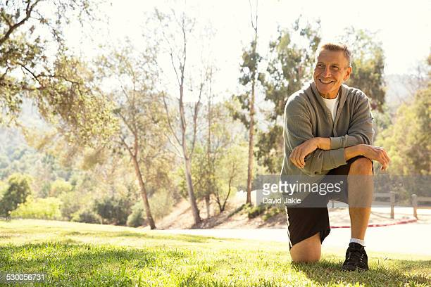 Portrait of mature male runner on one knee in park