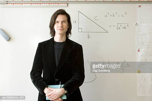 Portrait of mature male teacher in front of whiteboard