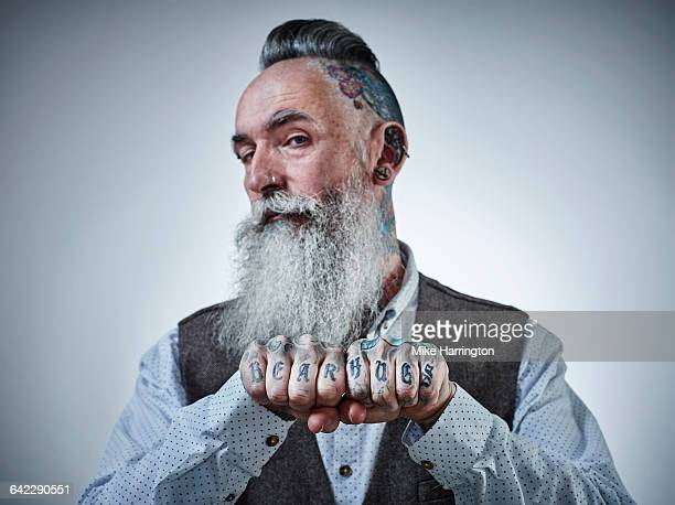 Portrait of mature male with tattooed fists