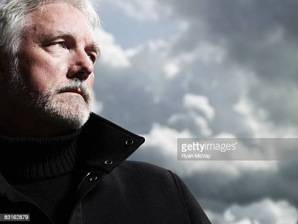 Portrait of mature man against stormy sky.