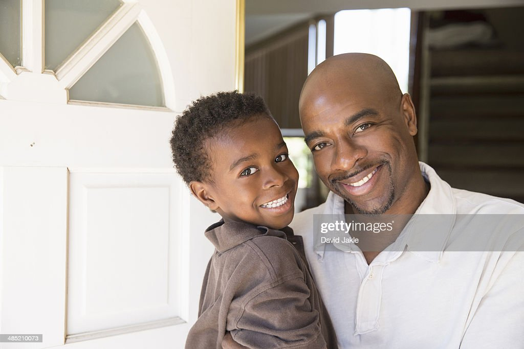 Portrait of mature man and son at front door