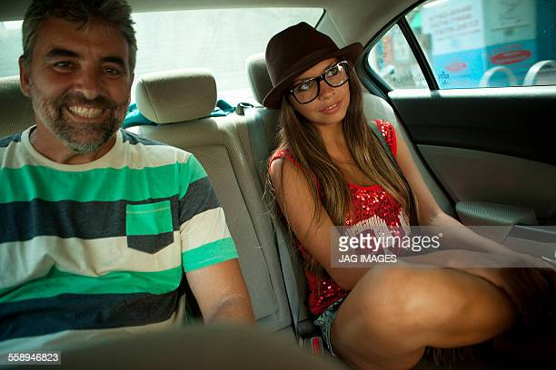 Portrait of mature man and young woman in back seat of taxicab, Rio De Janeiro, Brazil