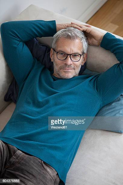 Portrait of mature man at home lying on couch