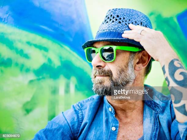 Portrait of mature man, graffiti on background