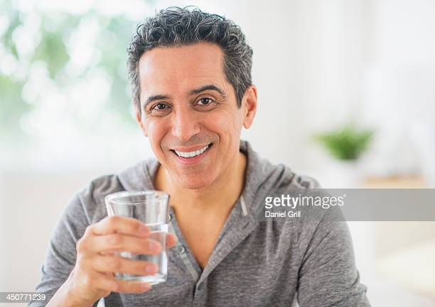 Portrait of mature man holding glass of water