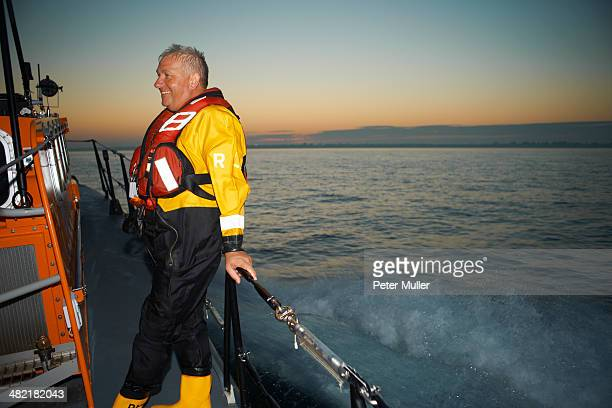 Portrait of mature man holding lifeboat railing at sea