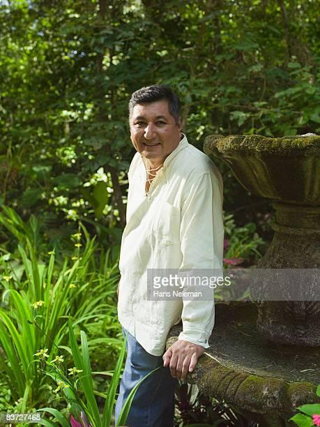 Portrait of mature man in lush garden