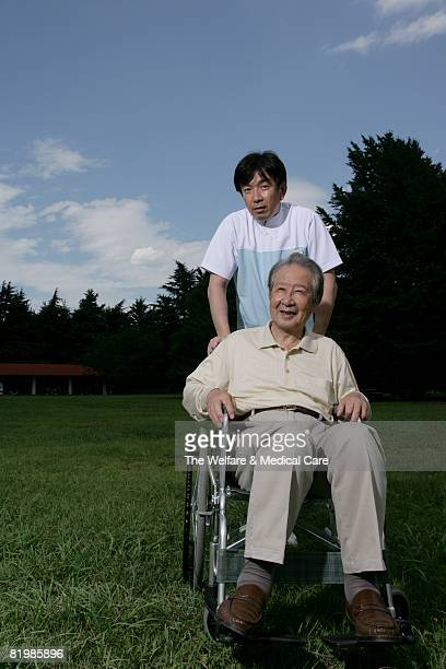 Portrait of mature man in wheelchair with male nurse