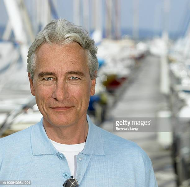 Portrait of mature man on jetty, sailboats in background