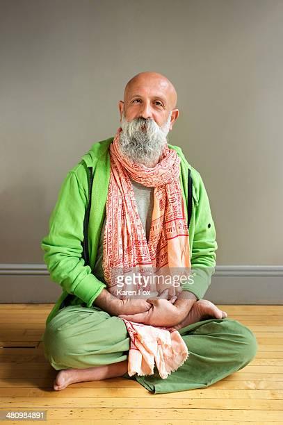 Portrait of mature man sitting in lotus pose on floor