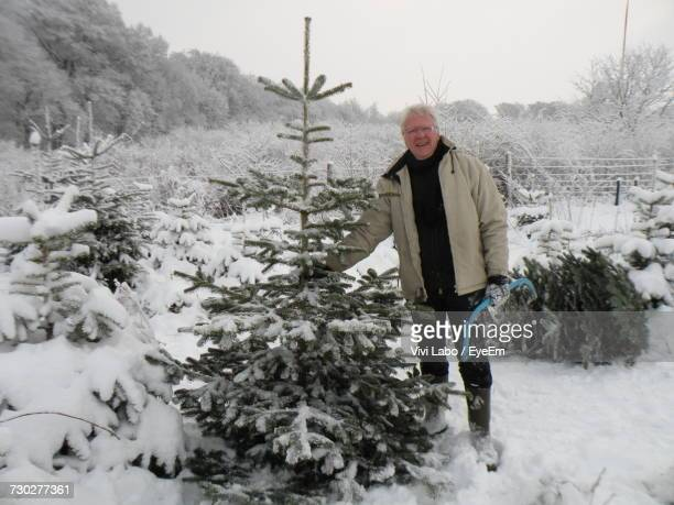 Portrait Of Mature Man Standing By Trees On Snow Covered Field