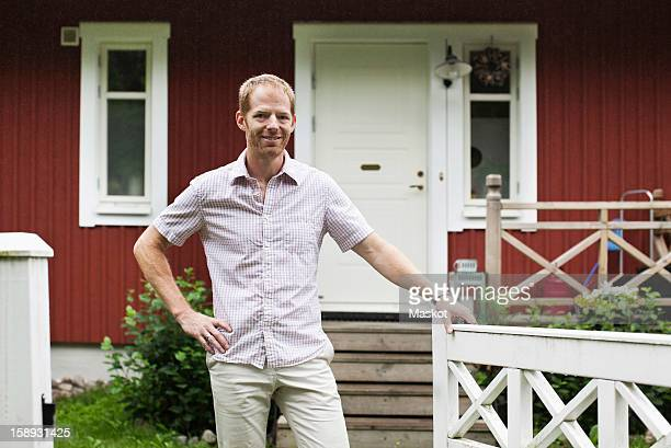 Portrait of mature man standing in front of house