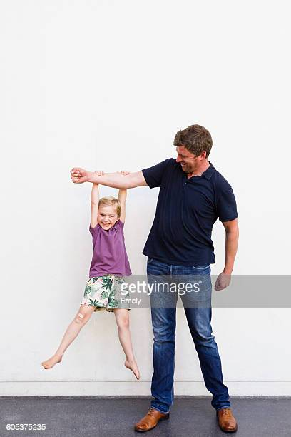 Portrait of mature man with daughter hanging from his arm in front of white wall