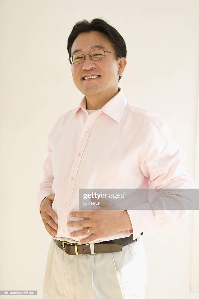 Portrait of mature man with hands on stomach : Stock Photo