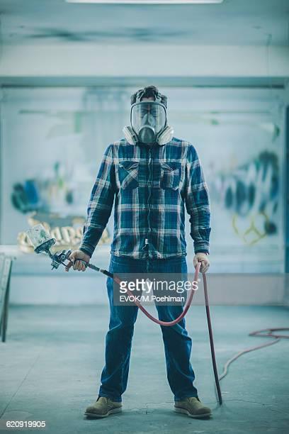Portrait of Mature Man with Spray gun in industrial spray paint room