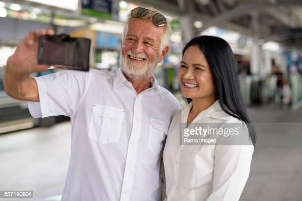 Portrait de couple multi-ethnique Senior heureux et amoureux à la station de skytrain BTS à Bangkok en Thaïlande