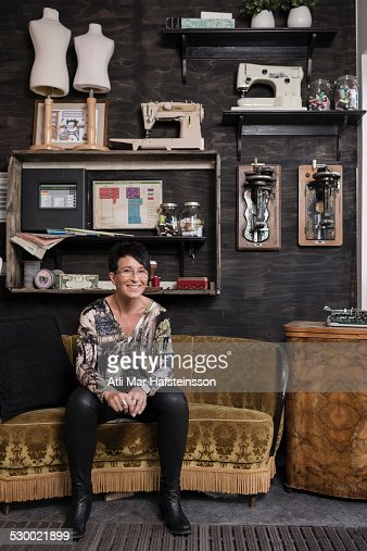 Portrait of mature seamstress sitting in quirky reception at workshop