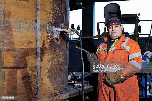 Portrait of mature welder in quarry workshop